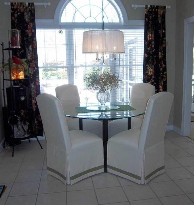 crescent back parsons chairs with banded skirts encircling a round table the contrasting band helps to set the chairs apart from the neutral colored floor